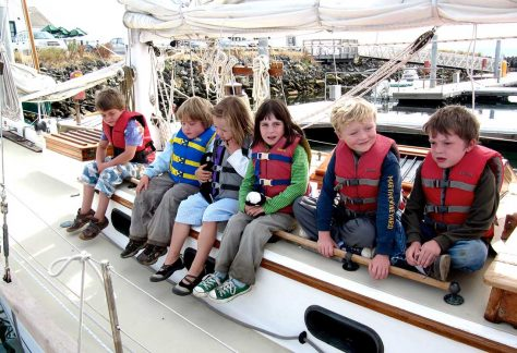 summer camp kids sit on sailboat