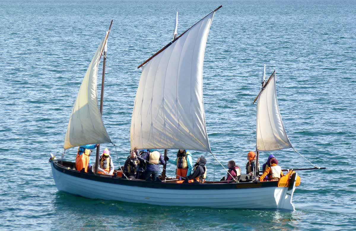 students sail on longboat in Port Townsend Bay
